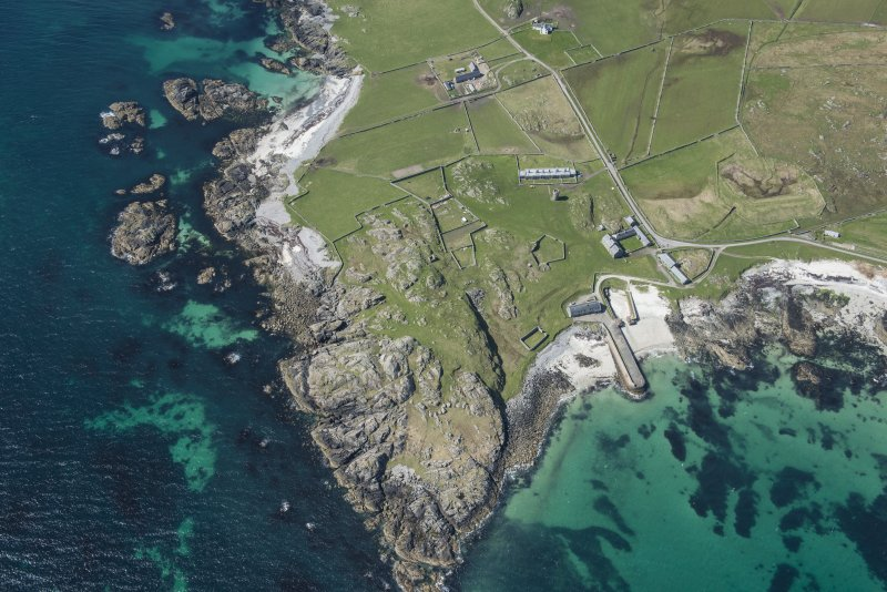 Oblique aerial view of Hynish Lighthouse shore establishment and harbour on Tiree, looking WSW.