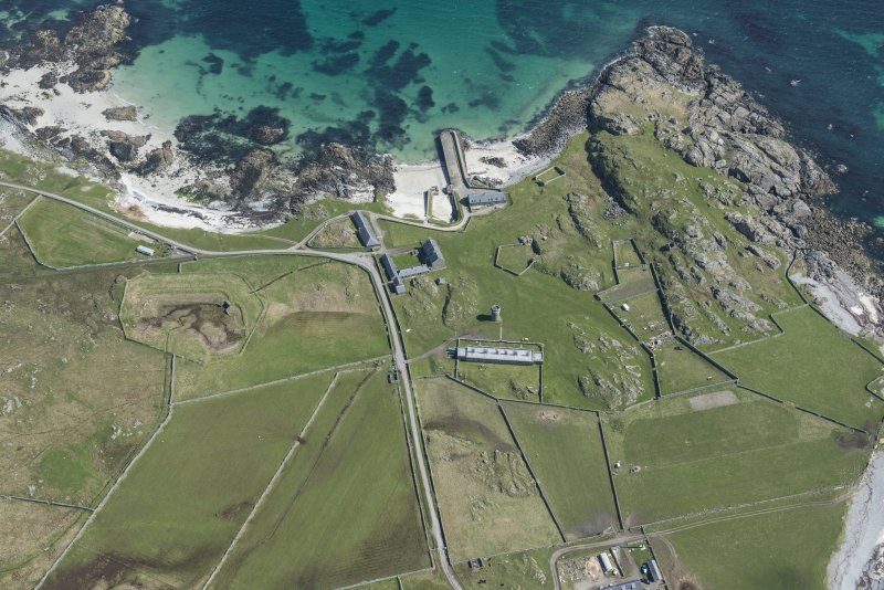Oblique aerial view of Hynish Lighthouse shore establishment, reservoir  and harbour on Tiree, looking ENE.