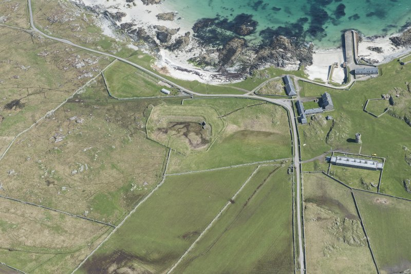 Oblique aerial view of Hynish Lighthouse shore establishment, reservoir  and harbour on Tiree, looking NE.