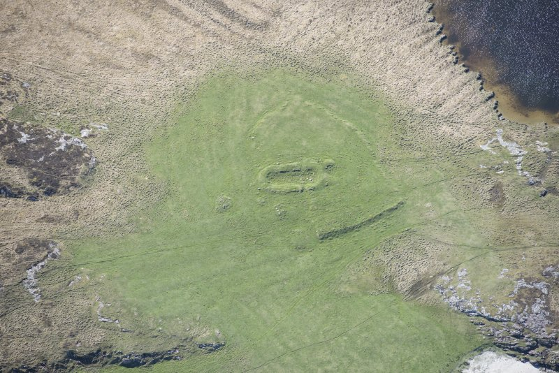 Oblique aerial view of a building lying within an area of rig and furrow at Loch Dubh a Gharaidh Fail on the Isle of Tiree, looking S.