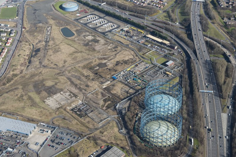 Oblique aerial view of Provan Gasworks including gasholders, looking ENE.