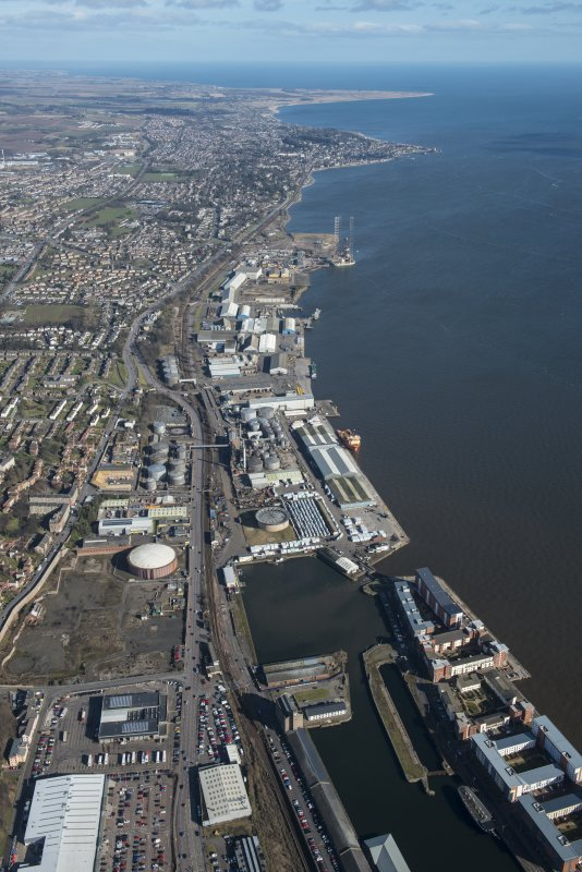 General oblique aerial view of the harbour area of Dundee centred on Camperdown Dock and King V Wharf, looking E.