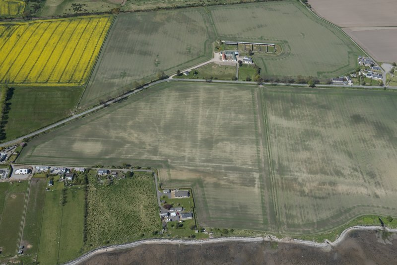 Oblique aerial view of the soilmarks at Polnicol, looking NW.