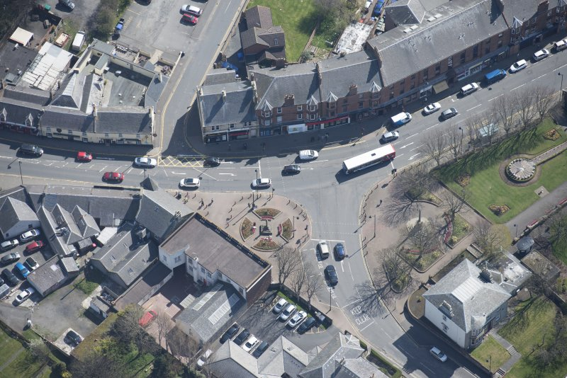 Oblique aerial view of Prestwick Market Cross, looking SE.