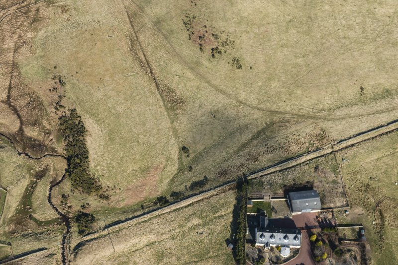 Oblique aerial view of the possible line of the Roman Road at Eight Mile Burn (NT 1930 5939), looking NNW.