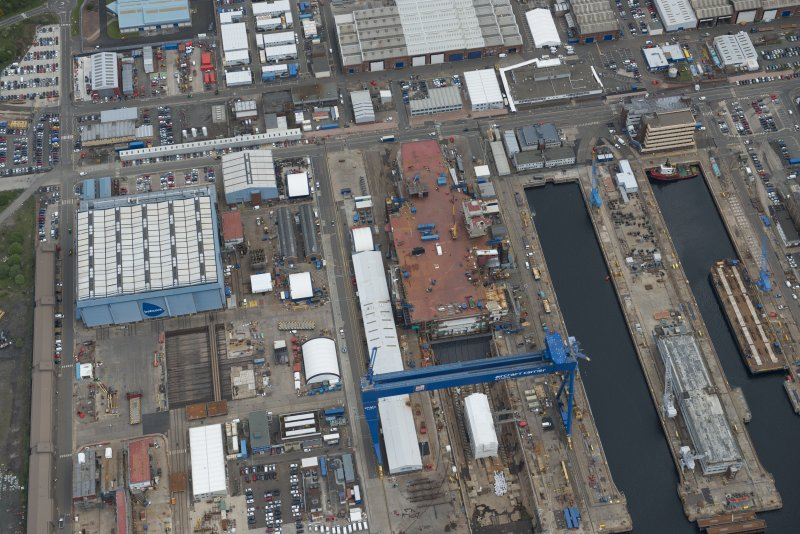 Oblique aerial view of Rosyth Naval Dockyard showing the construction of an aircraft carrier, looking NE.