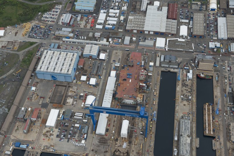Oblique aerial view of Rosyth Naval Dockyard showing the construction of an aircraft carrier, looking NNE.