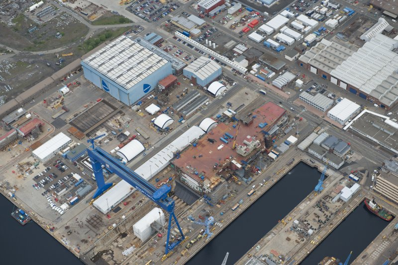 Oblique aerial view of Rosyth Naval Dockyard showing the construction of an aircraft carrier, looking NW.