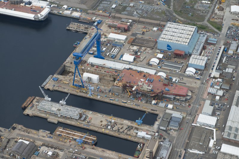 Oblique aerial view of Rosyth Naval Dockyard showing the construction of an aircraft carrier, looking W.