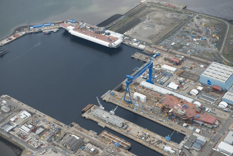 Oblique aerial view of Rosyth Naval Dockyard showing the construction of two aircraft carriers, looking W.