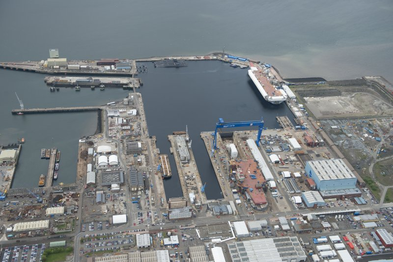 Oblique aerial view of Rosyth Naval Dockyard showing the construction of two aircraft carriers, looking SW.