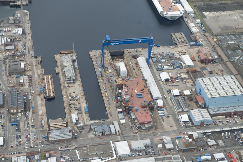 Oblique aerial view of Rosyth Naval Dockyard showing the construction of an aircraft carrier, looking S.