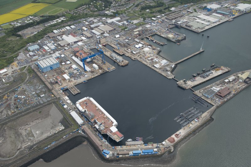 Oblique aerial view of the Main Basin, Rosyth Naval Dockyard showing the construction of two aircraft carriers, looking NE.