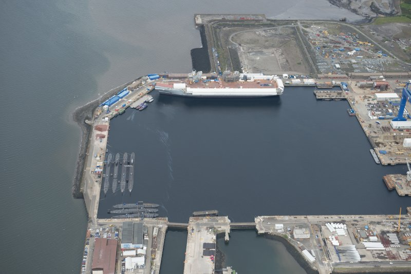 Oblique aerial view of the Main Basin, Rosyth Naval Dockyard showing the construction of an aircraft carrier, looking W.