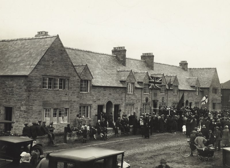 View of unidentified houses with crowd of people outside.