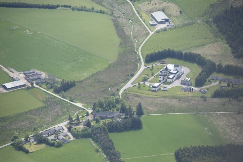 Oblique aerial view of the Braes of Glenlivet Distillery and Chapeltown Roman Catholic Church of Our Lady of Perpetual Succour, chapel house and burial ground, looking SE.