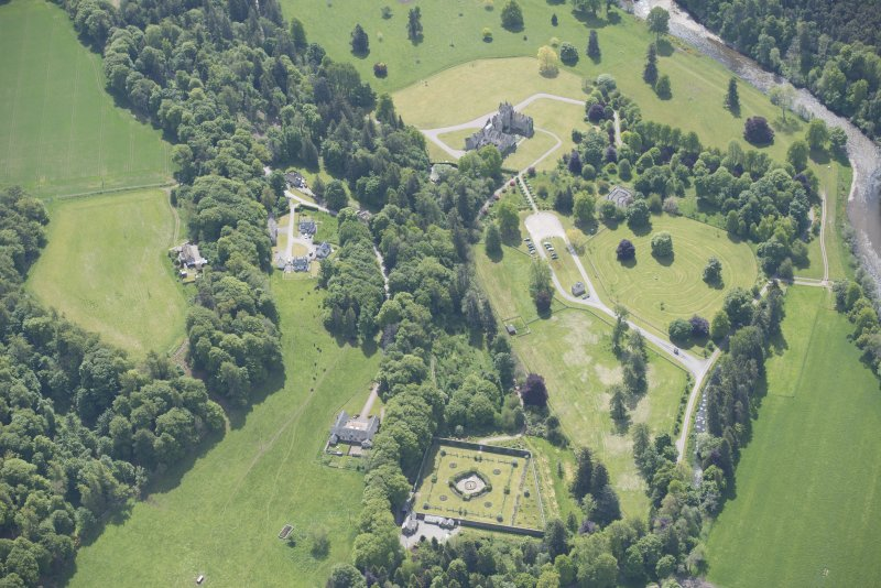 Oblique aerial view of Ballindalloch Castle, walled garden and stables, looking S.