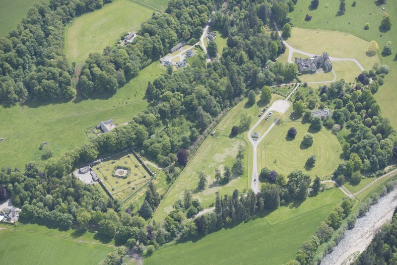 Oblique aerial view of Ballindalloch Castle, walled garden and stables, looking SE.