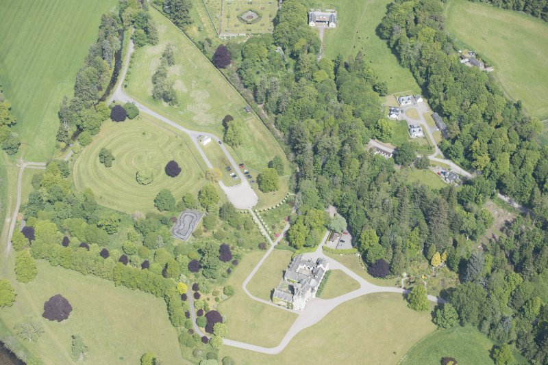 Oblique aerial view of Ballindalloch Castle and dovecot, looking NNE.