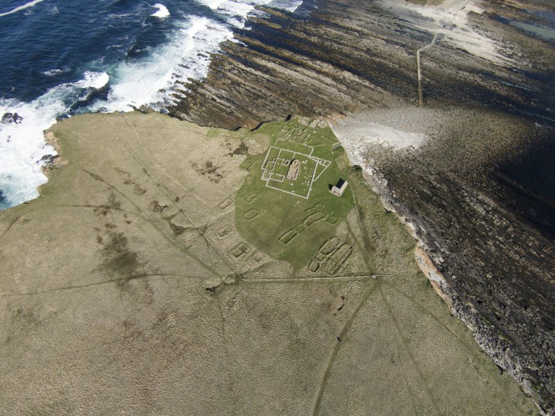 Oblique aerial view of the chapel and settlement at Brough of Birsay, looking E.
