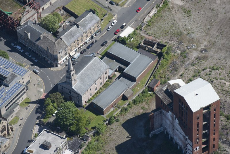 Oblique aerial view of Dumbarton Distillary and Riverside Parish Church, looking NE.