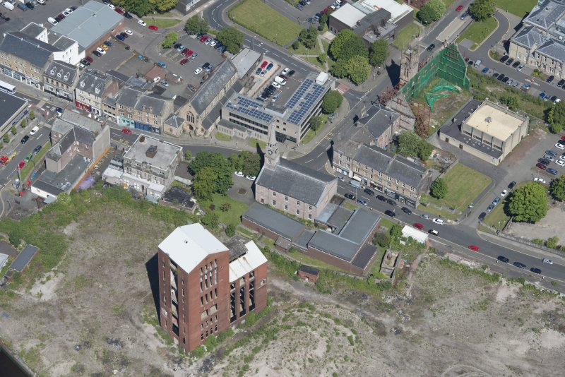 Oblique aerial view of Dumbarton Distillary and Riverside Parish Church, looking NW.