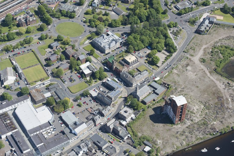 Oblique aerial view of Dumbarton Distillary, Riverside Parish Church, Dumbarton Academy and Burgh Halls, looking NE.