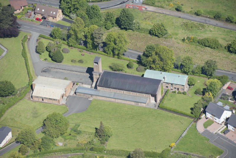 Oblique aerial view of the Holy Family Roman Catholic Church, looking N.