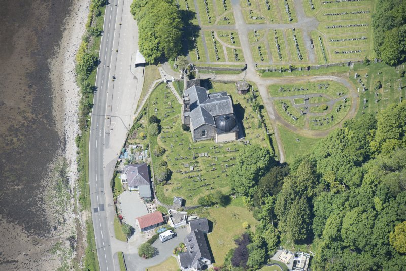 Oblique aerial view of Kilmun Cemetery, St Munn's Church, and Collegiate Church of St Mun, looking WNW.
