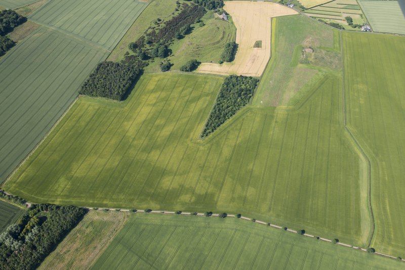 Oblique aerial view of the cropmarks of the ring ditch houses and the pit-defined boundary with The Chesters fort beyond, looking WSW.