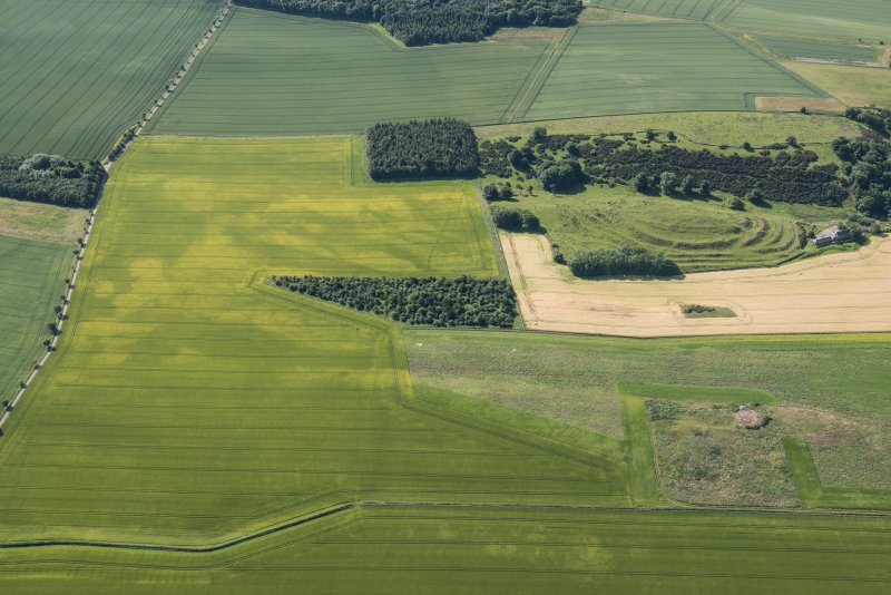 Oblique aerial view of the cropmarks of the ring ditch houses and the pit-defined boundary with The Chesters fort beyond, looking S.