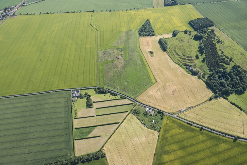 Oblique aerial view of the cropmarks of the ring ditch houses and the pit-defined boundary and The Chesters fort, looking ENE.