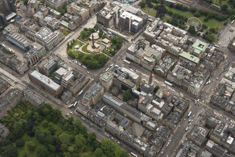 Oblique aerial view of George Street, Queen Street, Jenners Department Store, South St David Street and St Andrew Square, looking SE.
