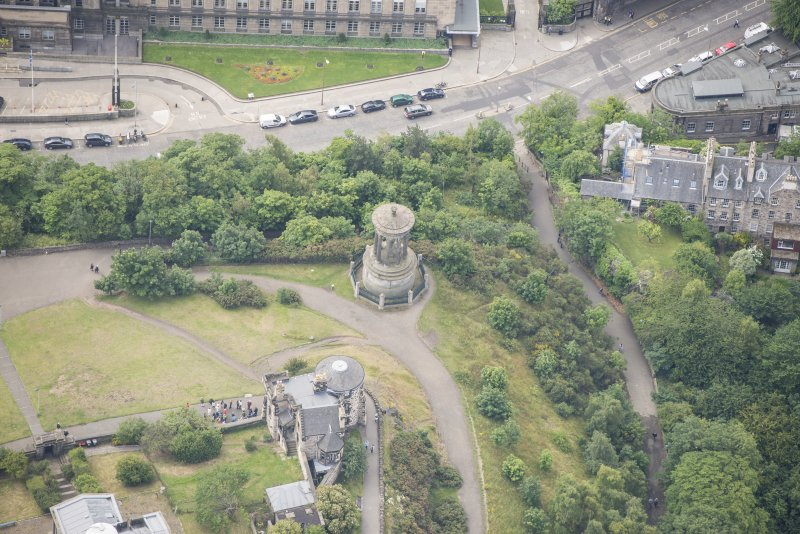 Oblique aerial view of the Dugald Stewart's Monument, Rock House and Observatory House, looking SSW.