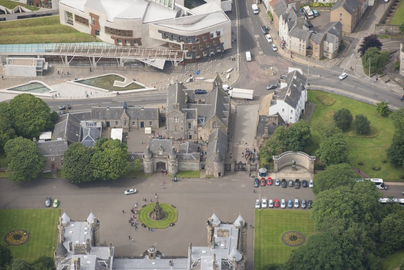 Oblique aerial view of Holyrood Palce gatehouse, Abbey Court, Holyrood Palace Yard fountain, Memorial to King Edward VII, Thomson's Court and 11, 13, 15 Canongate, looking WSW.