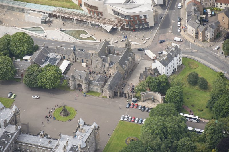 Oblique aerial view of the Memorial to King Edward VII, Thomson's Court, Holyrood Palace Gatehouse, Holyrood free Church and School, Abbey Sanctuary and Holyrood Palace Yard Fountain,  looking SW.