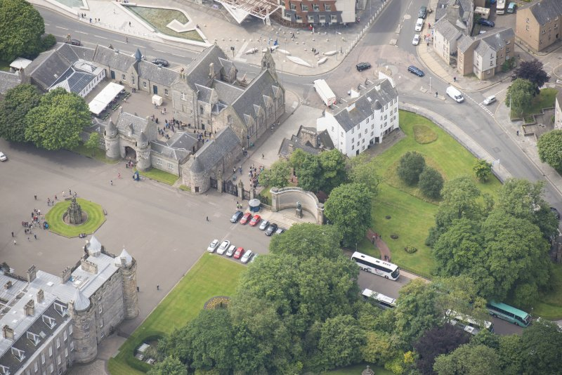 Oblique aerial view of Thomson's Court, Holyrood Palace Gatehouse, James IV's Tower Abbey Sanctuary, Holyrood Palace Yard Fountain and Holyrood Free Church and School, looking SSW.