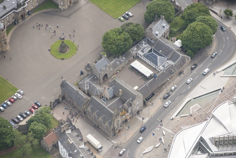 Oblique aerial view of Holyrood Free Church and School, Holyrood Palace Gatehouse and Holyrood Palace Yard Fountain, looking ESE.