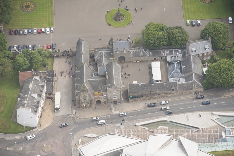 Oblique aerial view of Holyrood Palace Yard Fountain, Abbey Strand, Holyrood Palace Gatehouse, Holyrood Free Church and School, Thomson's Court and Abbey Sanctuary, looking ENE.
