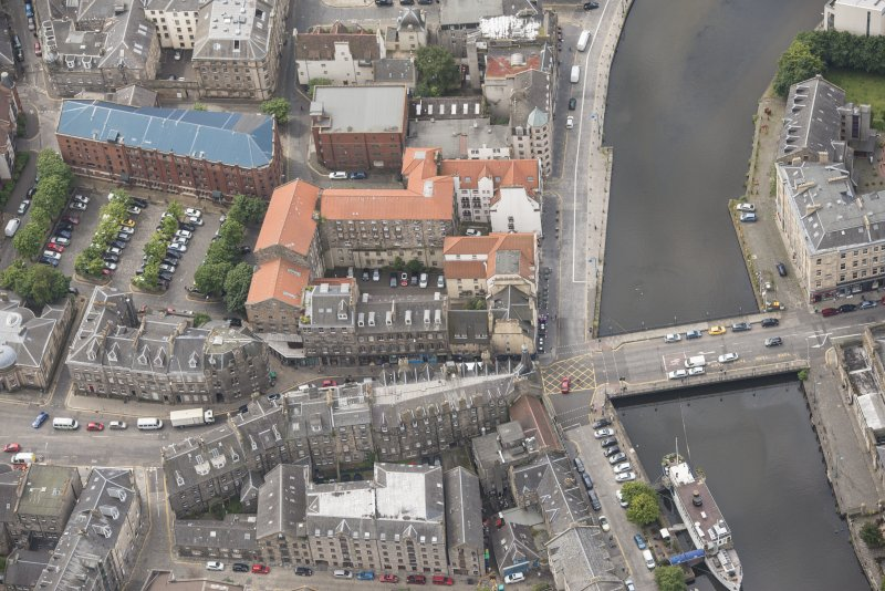 Oblique aerial view of 59-63 Bernard Street, the National Commercial Bank of Scotland, 24-25 Maritime Street, 27-31 Bernard Street, 36-37 Shore, Carpet Lane Flour Mill and Lamb's House, looking SSW.
