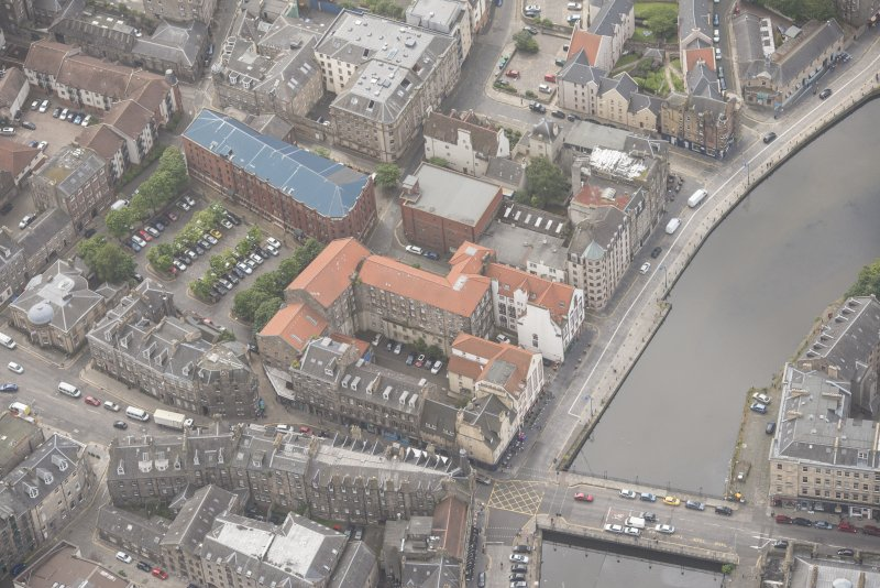 Oblique aerial view of 59-63 Bernard Street, the National Commercial Bank of Scotland, 24-25 Maritime Street, 27-31 Bernard Street, 36-37 Shore, Carpet Lane Flour Mill and Lamb's House, looking S.