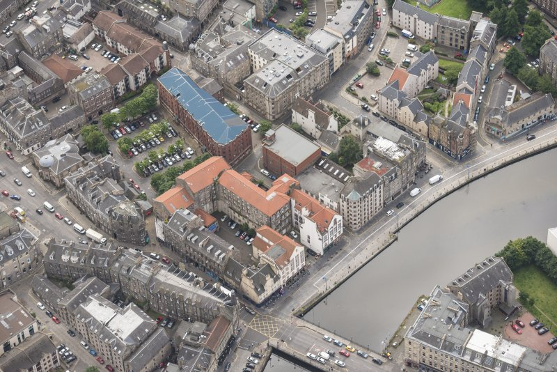 Oblique aerial view of 59-63 Bernard Street, the National Commercial Bank of Scotland, 24-25 Maritime Street, 27-31 Bernard Street, 36-37 Shore, Carpet Lane Flour Mill and Lamb's House, looking SSE.