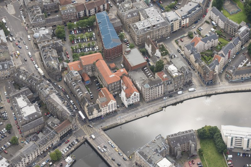 Oblique aerial view of 59-63 Bernard Street, the National Commercial Bank of Scotland, 24-25 Maritime Street, 27-31 Bernard Street, 36-37 Shore, Carpet Lane Flour Mill and Lamb's House, looking SE.