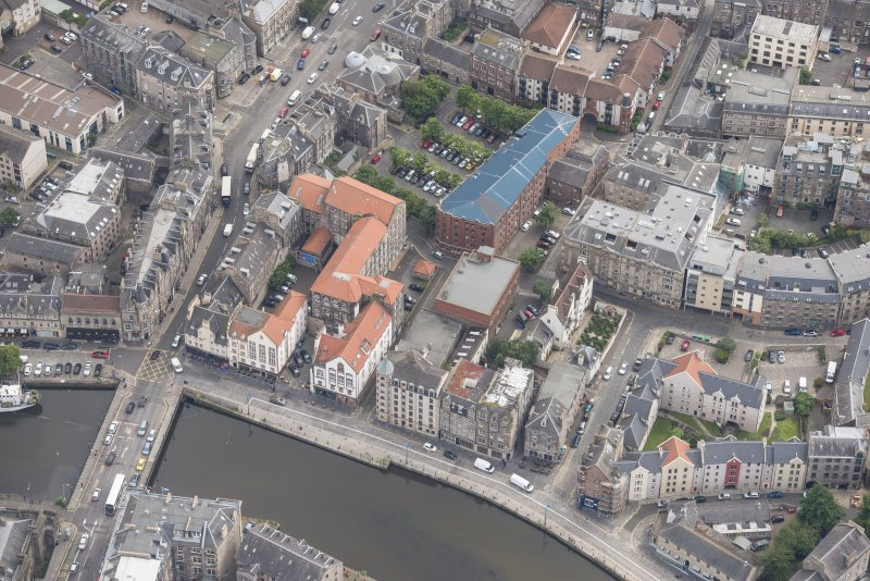 Oblique aerial view of 59-63 Bernard Street, the National Commercial Bank of Scotland, 24-25 Maritime Street, 27-31 Bernard Street, 36-37 Shore, Carpet Lane Flour Mill and Lamb's House, looking E.