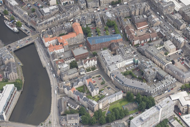 Oblique aerial view of 59-63 Bernard Street, the National Commercial Bank of Scotland, 24-25 Maritime Street, 27-31 Bernard Street, 36-37 Shore, Carpet Lane Flour Mill and Lamb's House, looking NE.