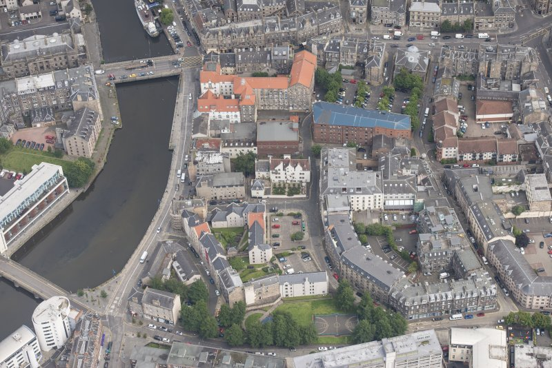 Oblique aerial view of 59-63 Bernard Street, the National Commercial Bank of Scotland, 24-25 Maritime Street, 27-31 Bernard Street, 36-37 Shore, Carpet Lane Flour Mill and Lamb's House, looking NNE.