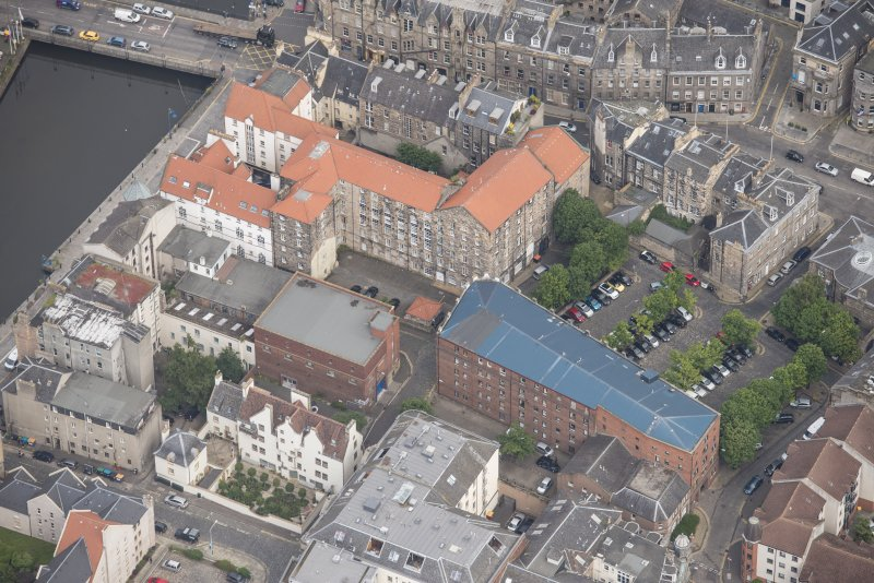 Oblique aerial view of 59-63 Bernard Street, the National Commercial Bank of Scotland, 24-25 Maritime Street, 27-31 Bernard Street, 36-37 Shore, Carpet Lane Flour Mill and Lamb's House, looking N.