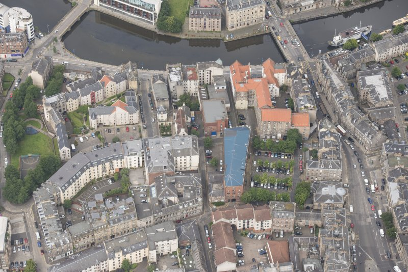 Oblique aerial view of 59-63 Bernard Street, the National Commercial Bank of Scotland, 24-25 Maritime Street, 27-31 Bernard Street, 36-37 Shore, Carpet Lane Flour Mill and Lamb's House, looking NW.