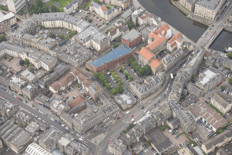 Oblique aerial view of 59-63 Bernard Street, the National Commercial Bank of Scotland, 24-25 Maritime Street, 27-31 Bernard Street, 36-37 Shore, Carpet Lane Flour Mill and Lamb's House, looking W.