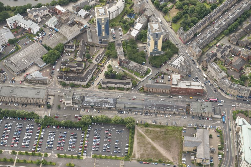 Oblique aerial view of 144-146 Commercial Street Bonded Warehouses, former Leith Nautical College, A&R Tod Flour Mill, 1-7 North Junction Street, 148 Commercial Street Warehouse and 142 Commercial Street Cooperage, looking SSW.